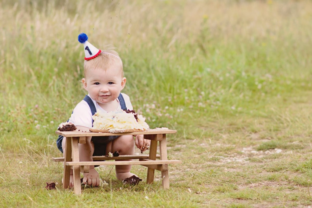 Baby Hero smashing his first birthday cake in a meadow
