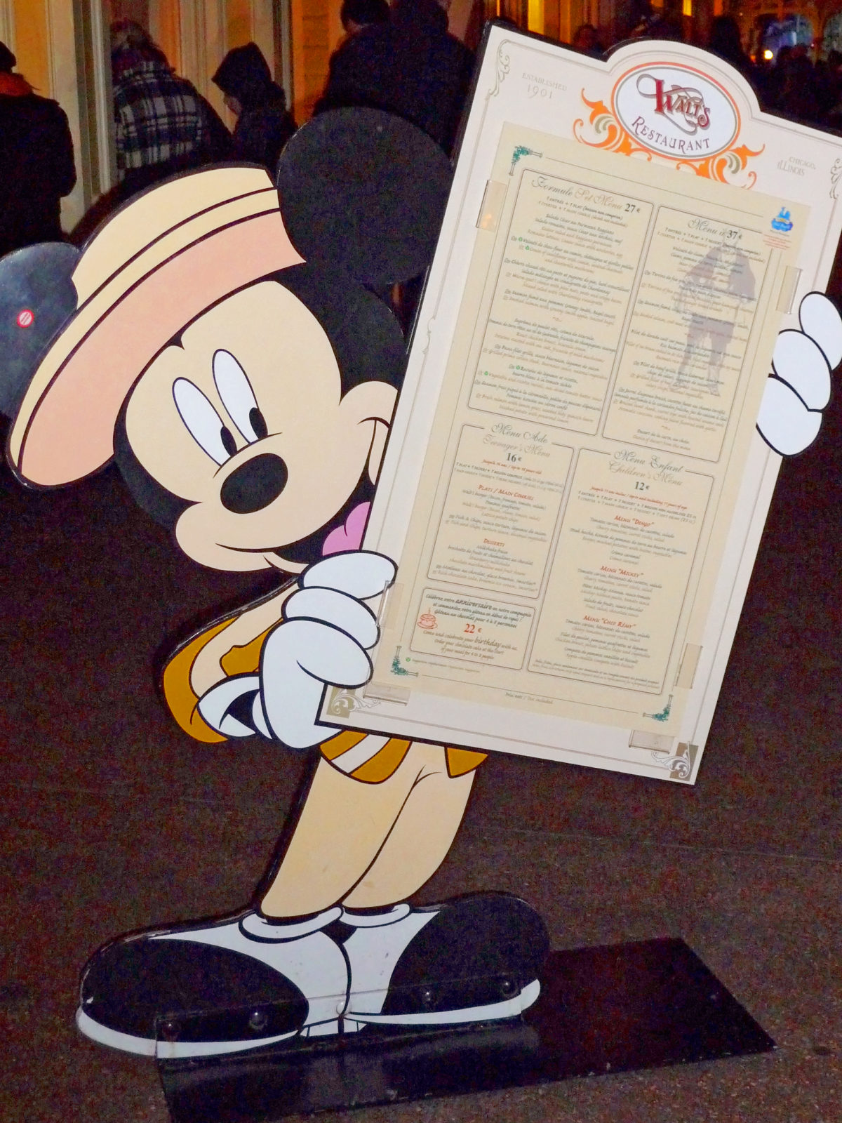 Image shows Mickey Mouse sign holding the menu for walt's restaurant in disneyland paris.