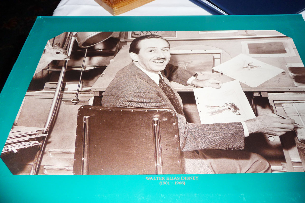 Image shows the inside of the menu at walts restaurant in disneyland paris. There is a photo of walt animating and holding a drawing of bambi.