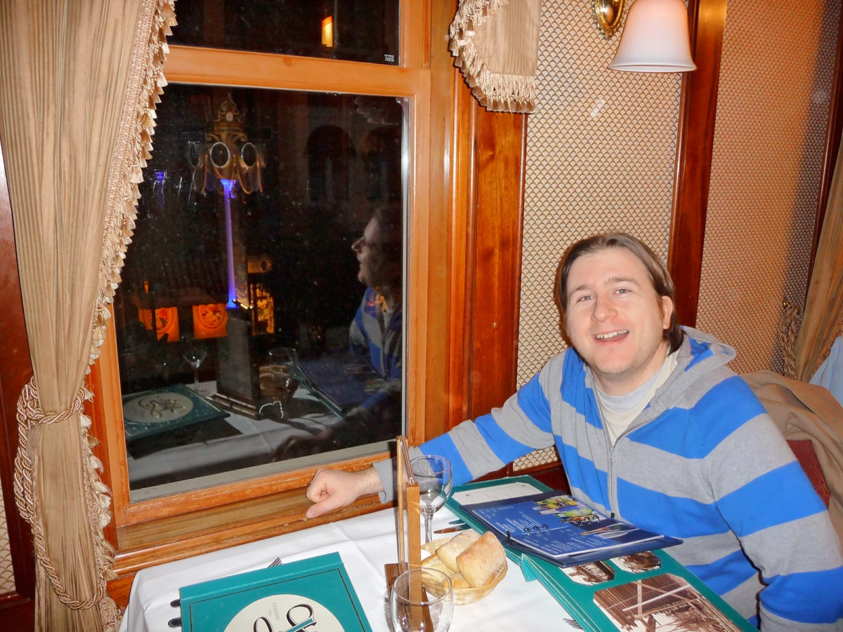 image shows a young man seated in the upstairs window of walt's restaurant in disneyland paris. He is reading the teal coloured menu and has bread rolls on the table.