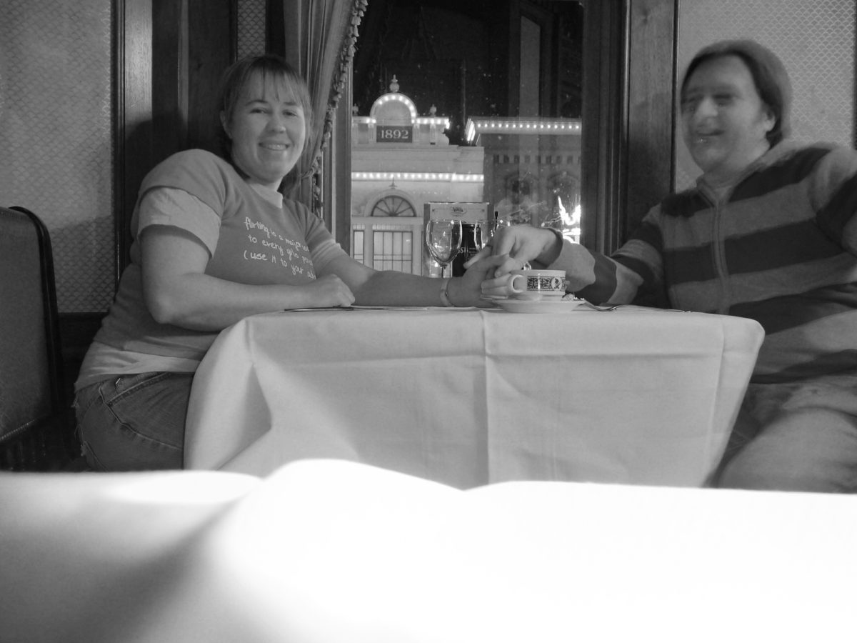 Image is a black and white photograph of a couple seated at walt's restaurant on the upper level in disneyland paris at night.