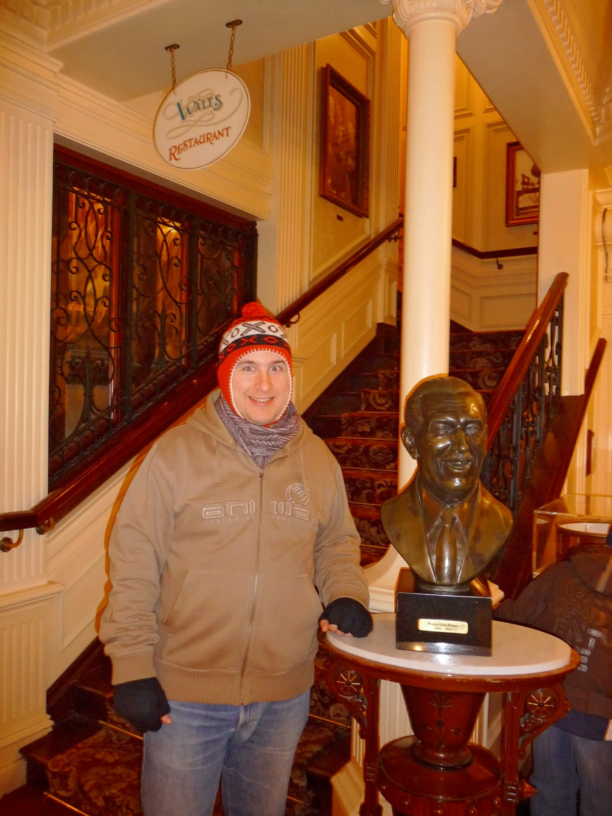 Image shows the bust of walt's head inside Walt's Restaurant in disneyland paris. A man is stood next to it, and he is dressed in warm winter clothes and a hat.