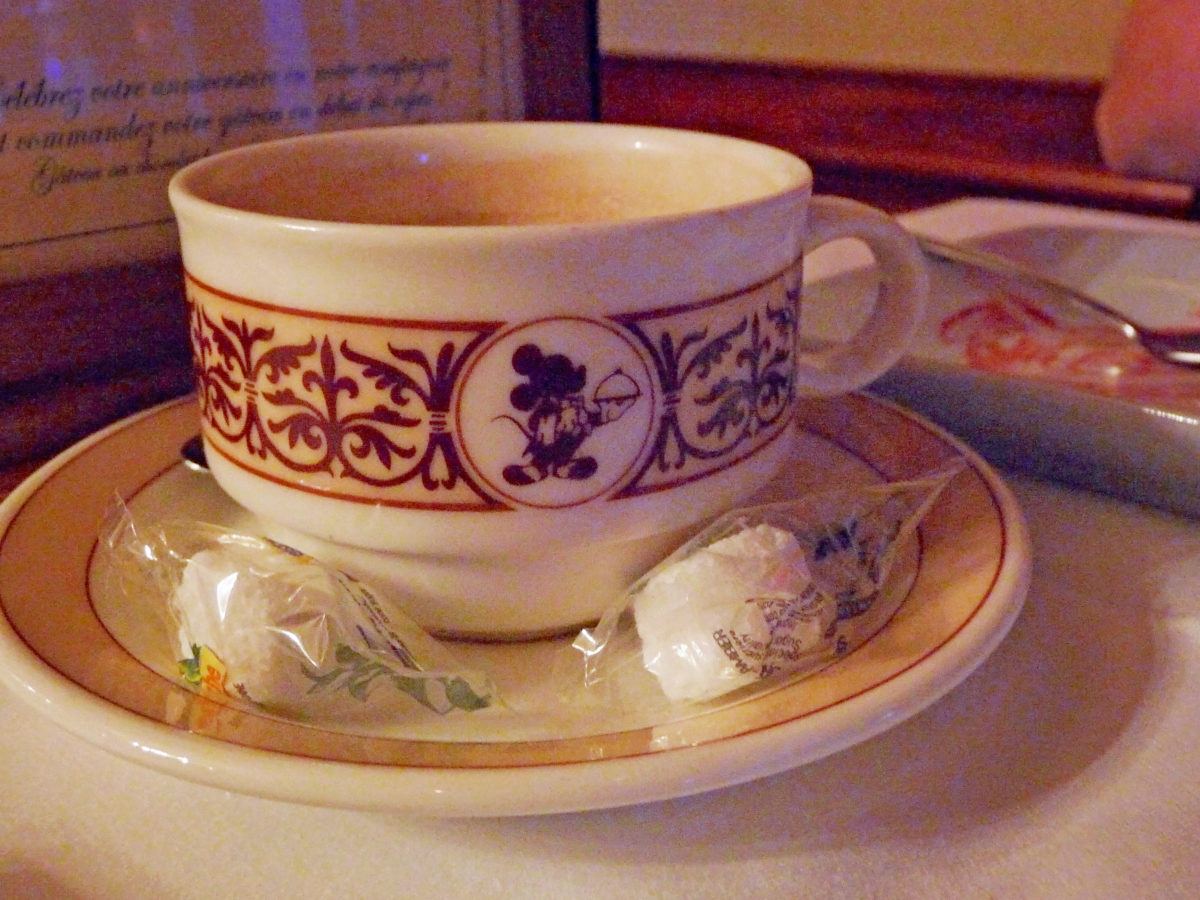 Image shows a coffee cup an saucer with Mickey Mouse as a fine dining server illustrated on the side.  There are two sugar cubes in plastic wrappers on the saucer.