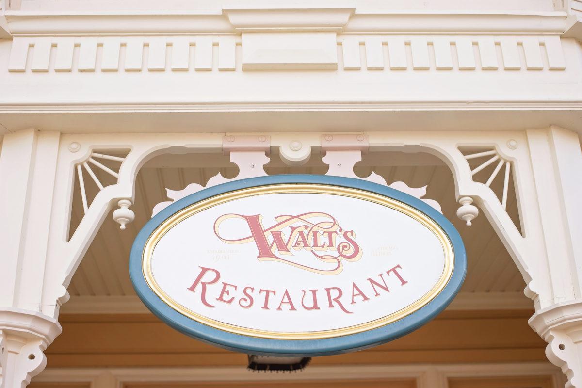 Image shows Walt's Restaurant sign on main street in disneyland paris.