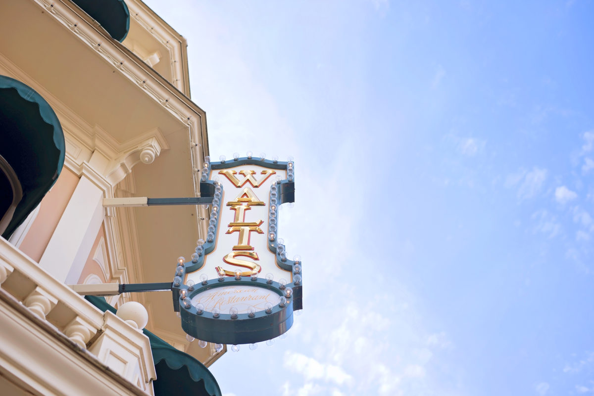 Image shows Walt's pink and green and gold Restaurant Signage on the side of main street building in Disneyland Paris. The sky is blue.