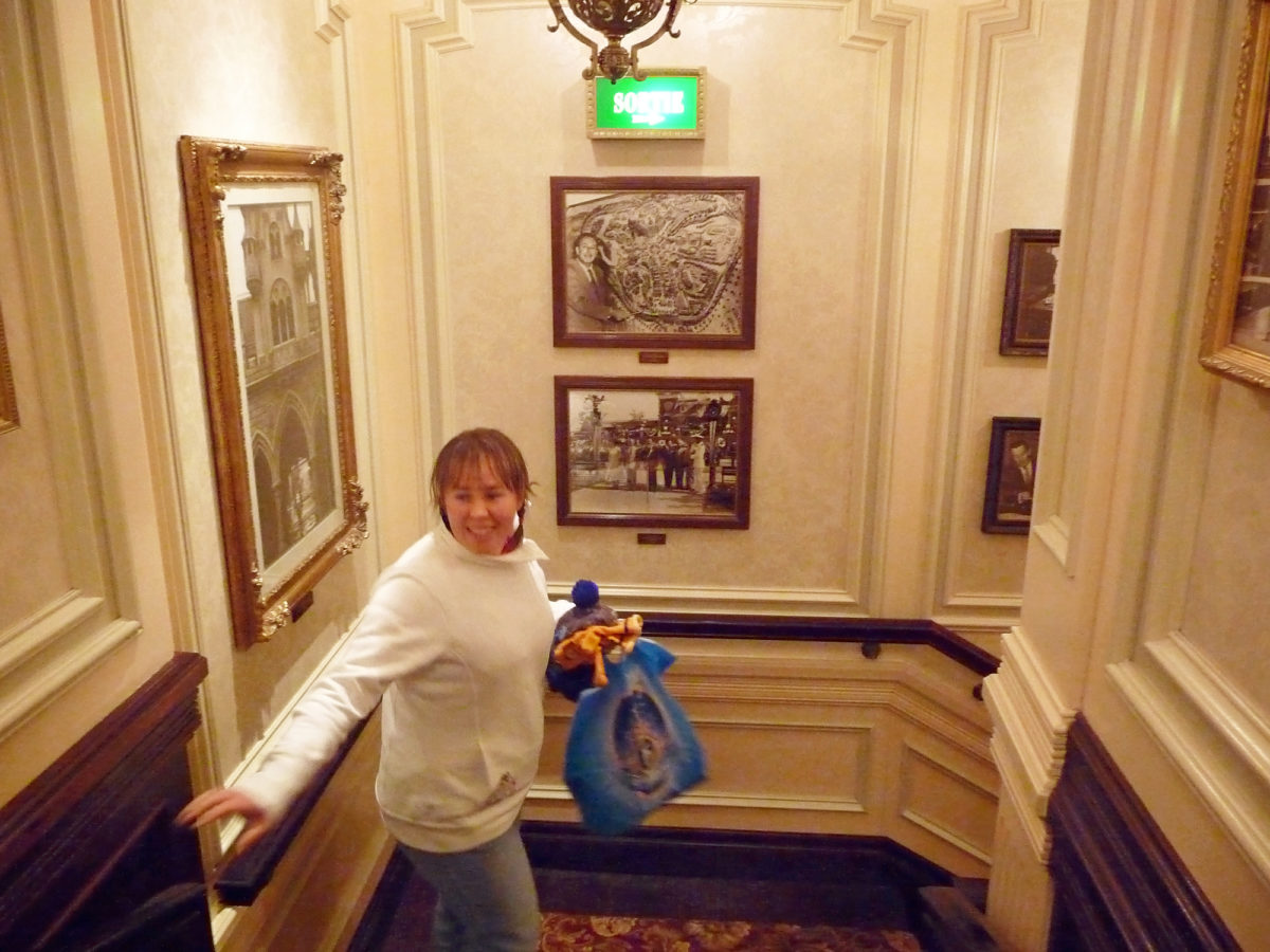 Image shows the interior of the staircase at Walt's restaurant in Disneyland Paris. There are photographs of Disney days gone by on the walls and a women is looking at them as she holds tigger gloves in her hand an a disneyland paris shopping bag.