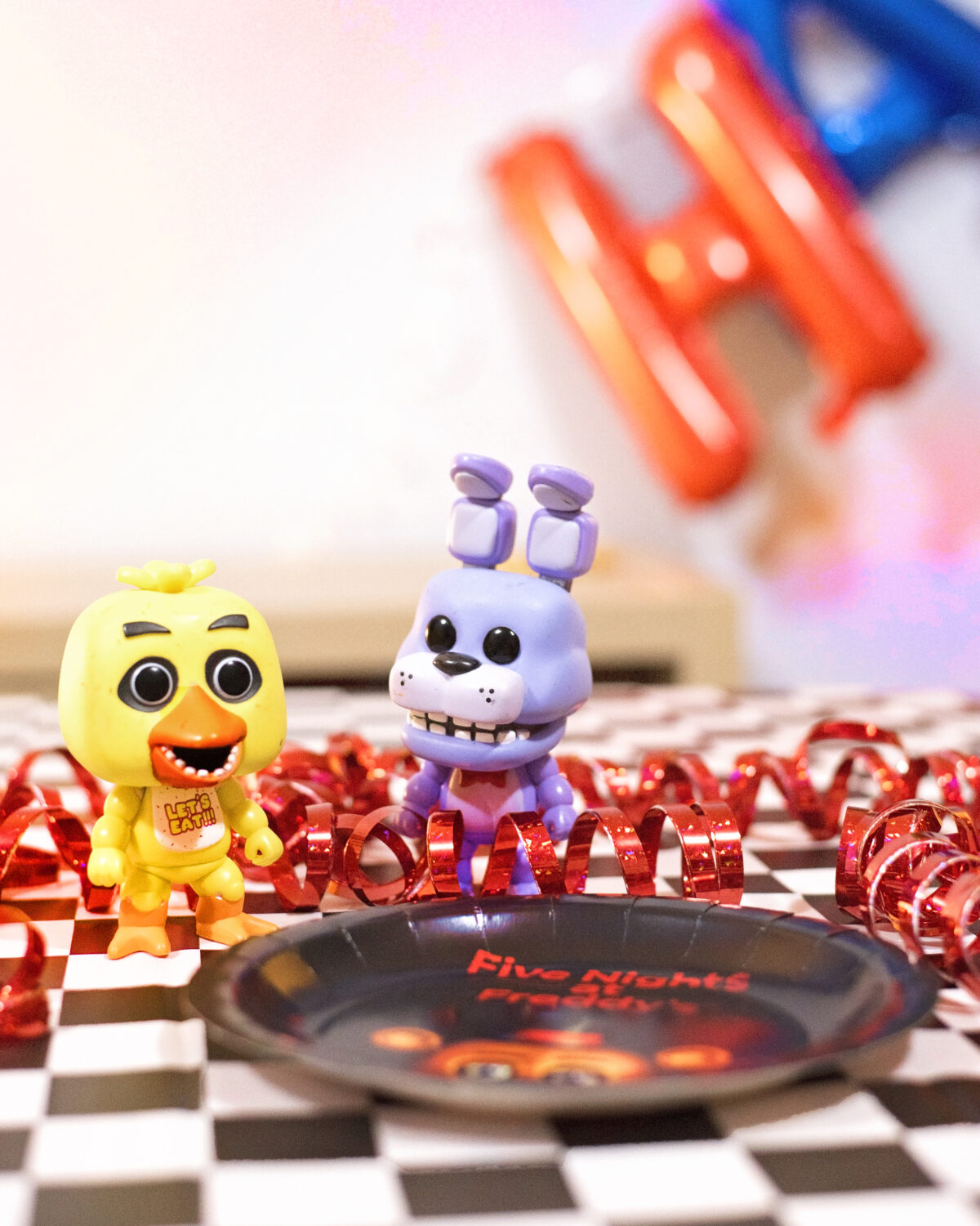 Image shows Party table close up of Pop Vinyl Five Nights at Freddy's figures Bonnie and Chica. They are surrounded by metallic red streamers and there are balloons in the background. Image by keep up with the jones family.