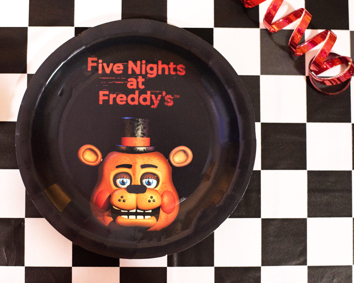 Image shows a checkered black and white tablecloth set with metallic red streamers and a black paper Five NIghts at Freddy's plate featuring Freddy Fazbear's face.  Image by keep up with the jones family.