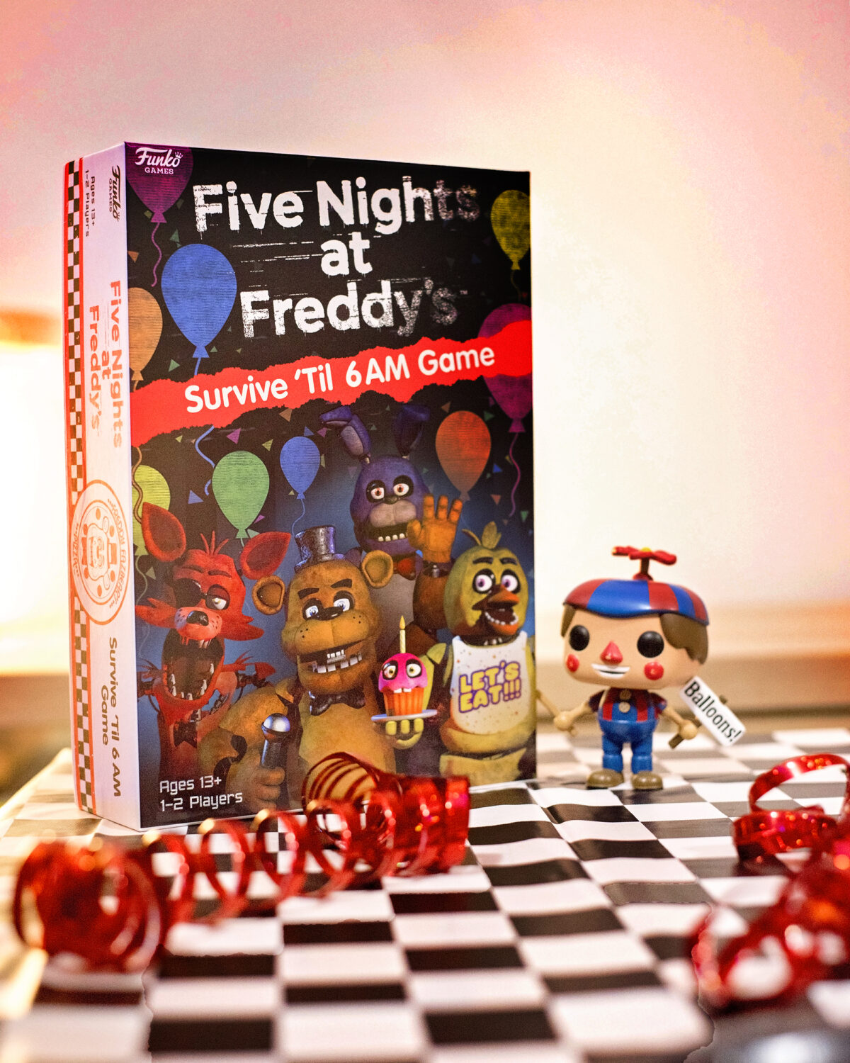 Image shows the Five Nights at Freddy's Survive 'til 6AM game on a table covered with a black and white checkered tablecloth, strewn with red metallic streamers and with a Funko Pop Vinyl figure of Balloon boy from FNAF stood next to the box. Image by keep up with the jones family.