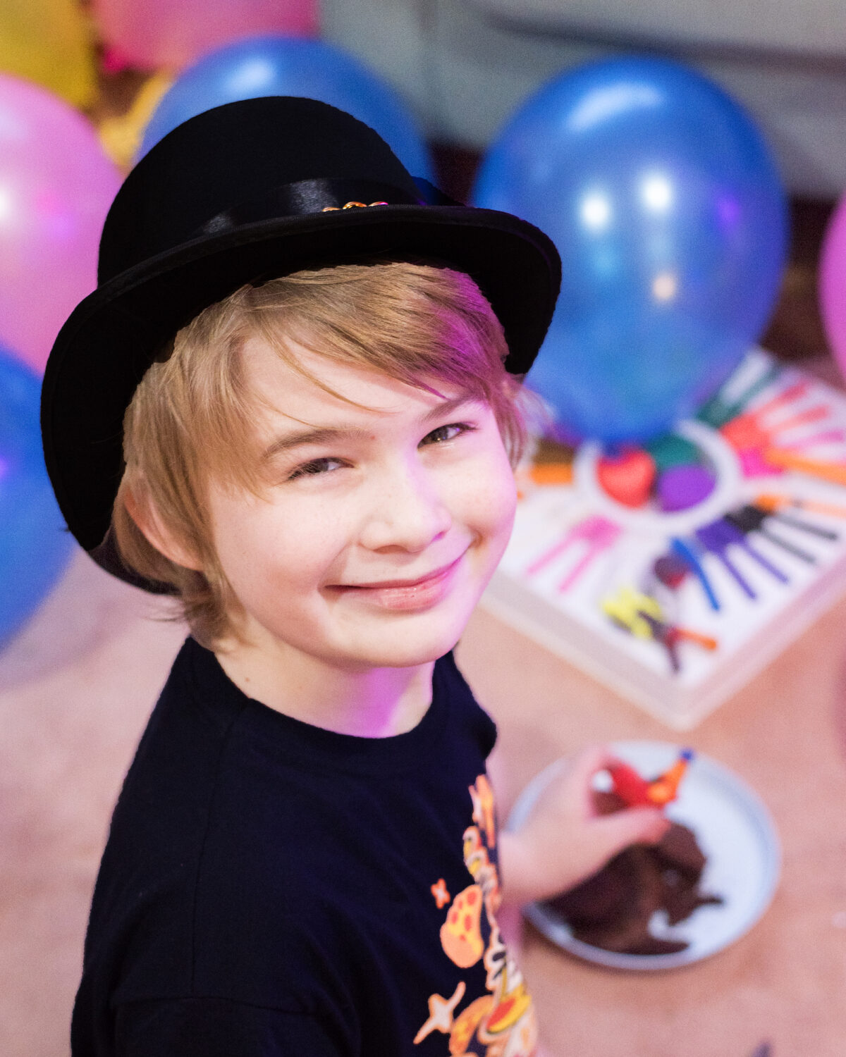 Image shows a happy boy smiling at the camera with a black top hat on. image by keep up with the jones family.
