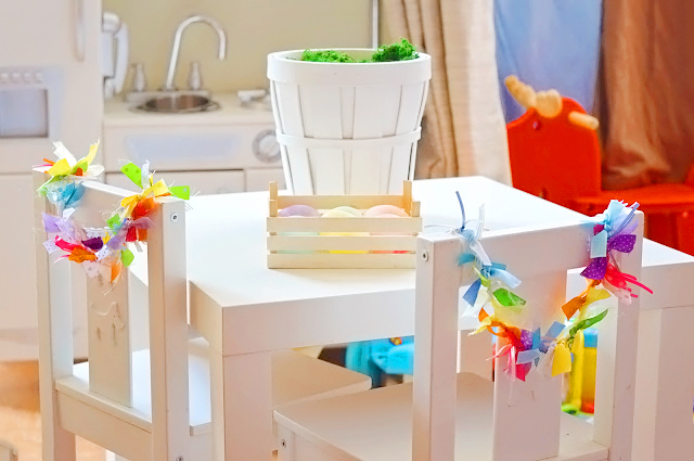 Image shows an easter table with a crate of coloured easter eggs ready for decorating.