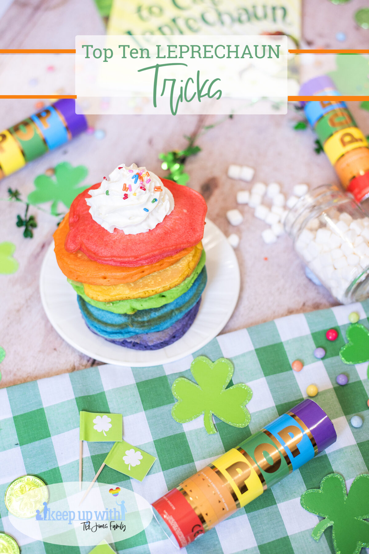 Top ten leprechaun tricks for st. patricks day. Image shows stack of rainbow pancakes on top of a St. Patrick's day tablescape.  Green checkered gingham tablecloth, leprechaun gold and rainbow confetti cannons.  There are little green flags featuring white shamrocks and glittery card shamrocks, rainbow coloured sweets and candies and a jar of spilled marshmallows.