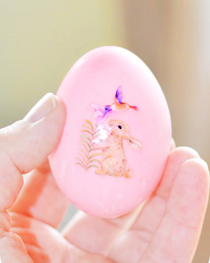 Image shows pink coloured duck egg, hollowed for easter. The candy pink easter egg has a sticker of a real rabbit  and some flowers.