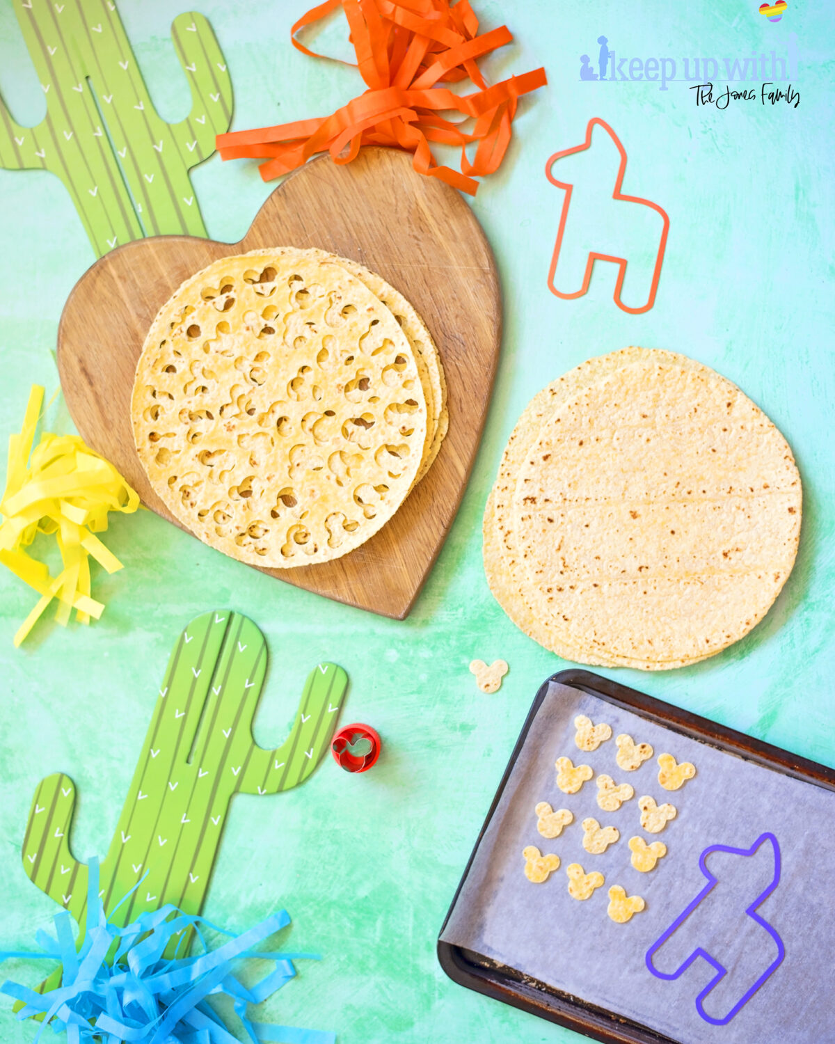 Image shows the recipe for Mickey Mouse taco chips. There is a baking tray with small cut out tortilla chips in the shape of Mickey Mouse's head. There is a metal Mickey Mouse cookie cutter and decorations for cinco de mayo, disney style.  There is a cardboard cactus and some tassles in bright colours on a sea green background.  Keep Up with the Jones Family.