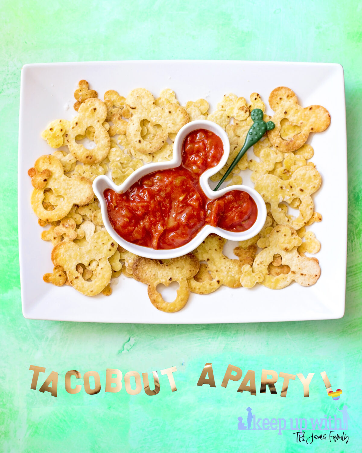 "Image shows large rectangular white plate filled with Disney's Mickey Mouse nacho chips and a Mickey Mouse shaped bowl of salsa.  The background is sea green and there is a golden banner across the bottom saying ""taco bout a party"" for cinco de mayo. Keep up with the jones family."