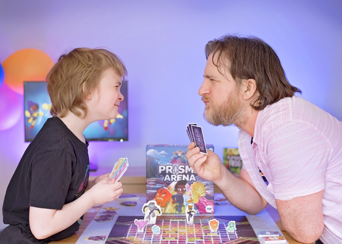 How to win Prisma Arena. Photo shows Dad and son head to head holding combo cards in their hands.