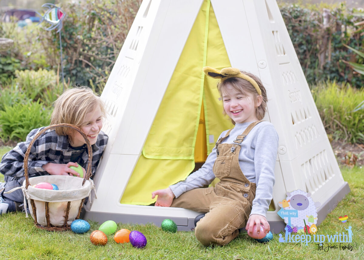 Image shows the new Smoby Teepee, available on Amazon, in the garden. The teepee is cream, white and green with a triangle pattern on the sides.  There is a fabric door which is lime green and two little boys are sat on the outside of the teepee, dressed for easter with bunny ears on.  They are laughing.  They have easter baskets filled with coloured easter eggs which have spilled onto the floor.  The teepee is decorated with a sign which reads Easter Bunny Stop here!