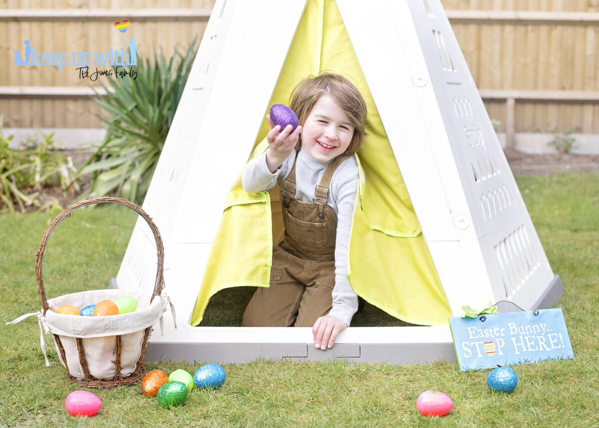 Image shows the new Smoby Teepee, available on Amazon, in the garden. The teepee is cream, white and green with a triangle pattern on the sides.  There is a fabric door which is lime green and a little boy with brown hair is sat in the doorway, dressed for easter and holding a purple glittery easter egg. He is laughing.  There is an easter basket filled with coloured easter eggs which have spilled onto the floor.  The teepee is decorated with a sign which reads Easter Bunny Stop here!