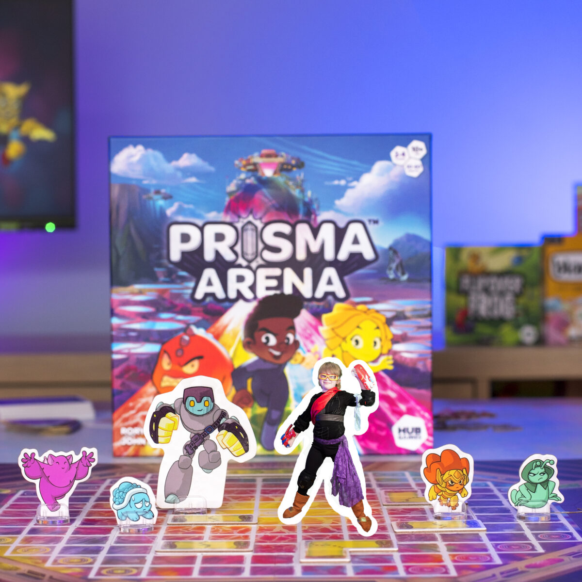 Prisma Arena Tabletop Game from Hub Games. Picture shows Heroes and Mo'kons from the game with a child posing as one of the game standee pieces.  The colours are bright and vivid.