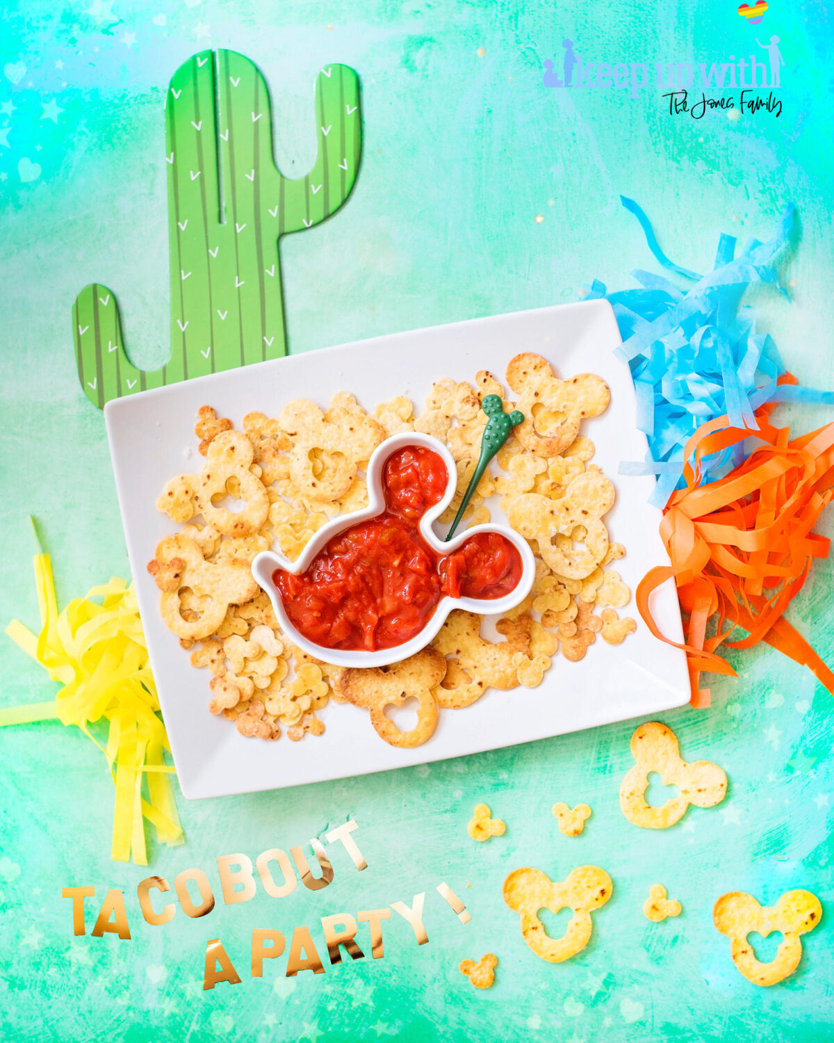 Image shows rectangular white plate filled with Mickey Mouse shaped tortilla chips and a Mickey Mouse head shaped salsa bowl. Surrounding the plate are cinco de mayo disney decorations. There are cardboard cactus and orange, blue and yellow pom pom tassles.  They are Mickey Mouse Nachos, fun food for children