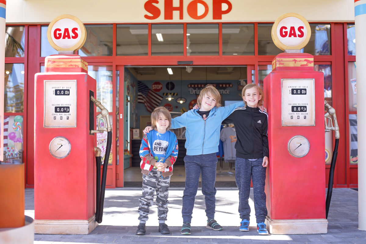 Image shows three boys from Keep Up With The Jones Family stood side by side between the themed entrance to Al's Shop in tornado springs at Paulton's Park in ower, Hampshire. There are two replica red retro gas pumps on either side of the boys.