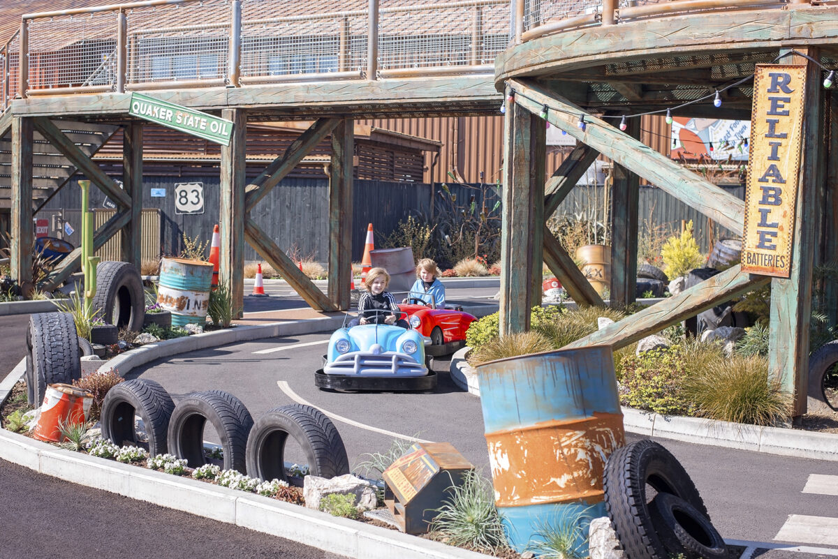 Image shows two little boys in cars driving around the track at Al's auto academy at Tornado Springs in Paultons Park.