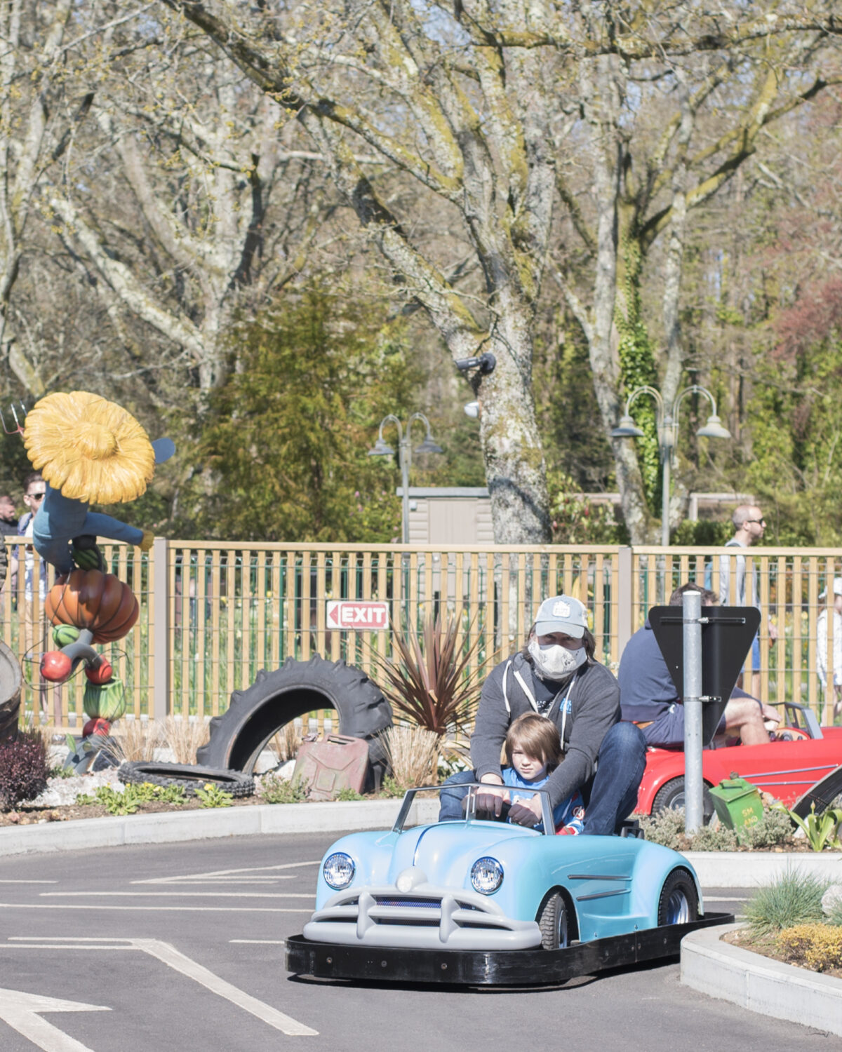 Image shows a parent and child driving a blue 1950s car in the Al's Automobile Academy attraction at Tornado Springs in Paultons Park.