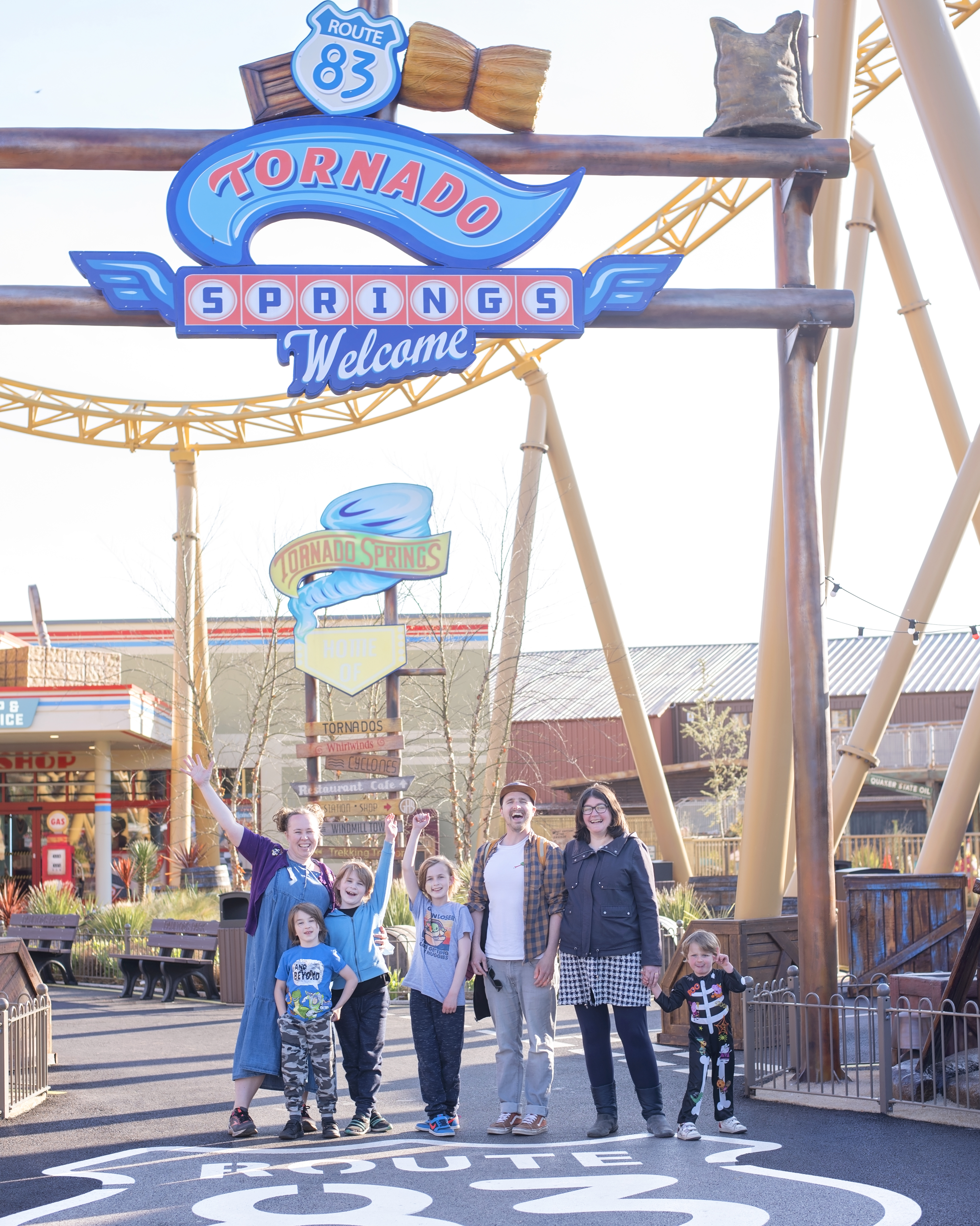 Image shows a family of seven stood underneath the Paultons park Tornado Springs rollercoaster and sign in ower, hampshire. The rollercoaster is the yellow storm chaser new for 2021 and on the floor is a large painted white route 83 logo.