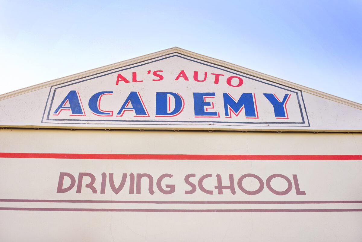 Image shows the signage on the building for Al's Auto Academy Driving School at Tornado Springs in Paultons Park.