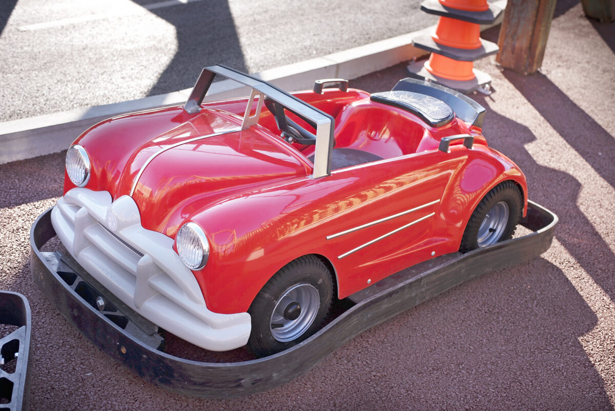 Image shows a red 1950's vehicle for children to drive at  Al's Auto Academy Driving School at Tornado Springs in Paultons Park.