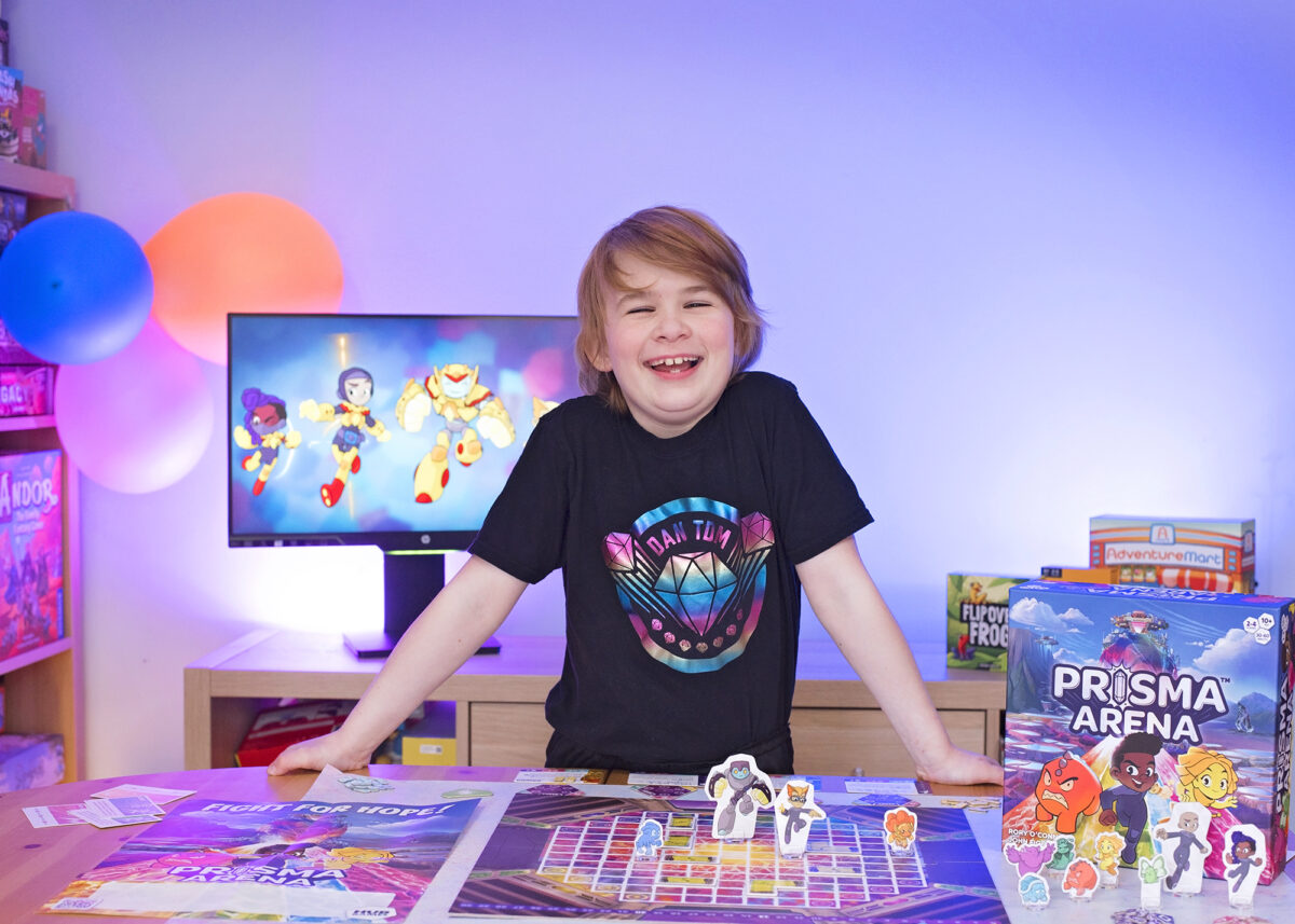 Photo shows a boy stood over a tabletop looking at the Prisma Arena Game set up.  He has blond hair and is smiling.  The boy is wearing a black Dan TDM t-shirt with a colourful foil diamond logo on it. The lighting in the photo is blue and behind the boy is a monitor displaying graphics from the Hug Games website.  Other Hub Games are in the background including Flip Over Frog and Adventure Mart.