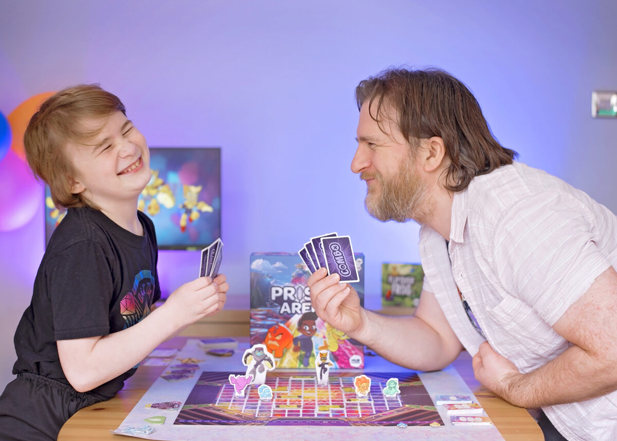 Photo shows father and son laughing whilst playing Prisma Arena from Hub Games. Board Game Geek.