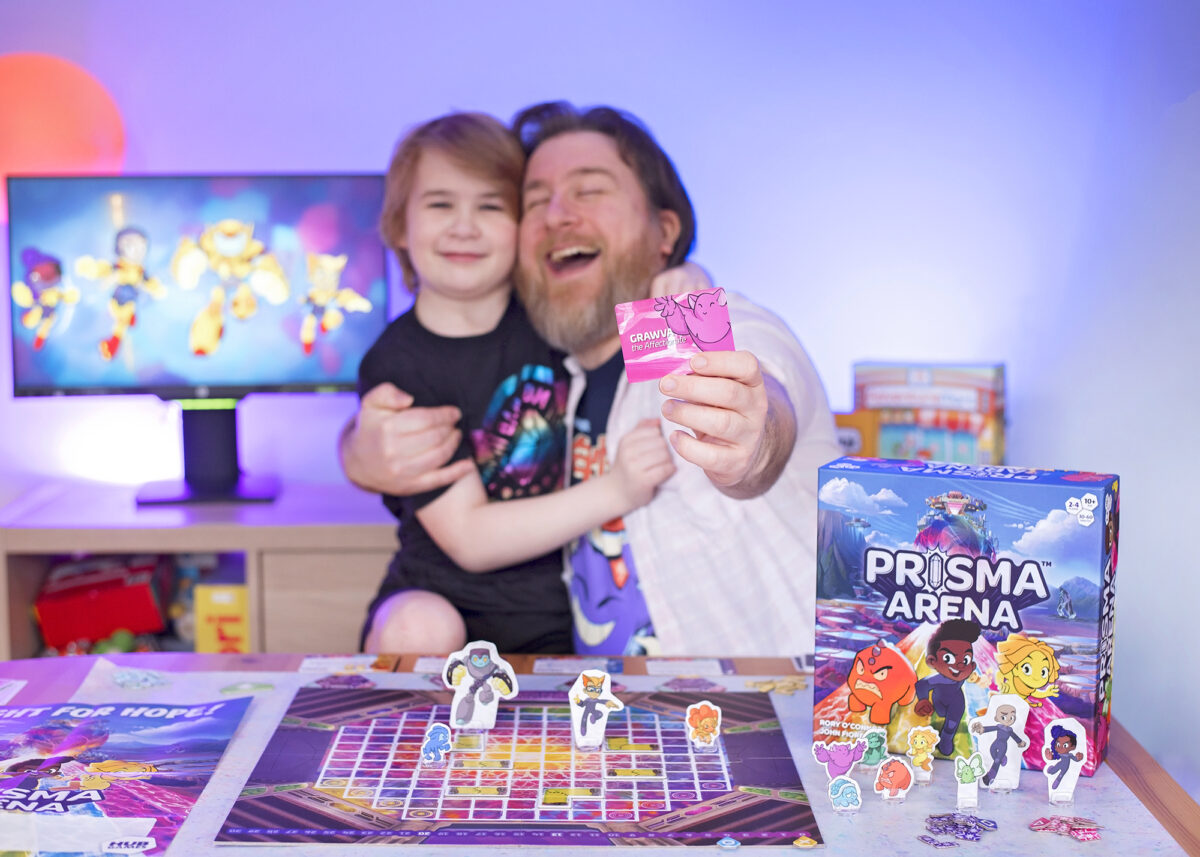 Prisma Arena Mo'kon Grawva brings grappling and hugs into the game from Hub Games. Photo shows Dad and Son hugging whilst holding out the Grawva card from the game.