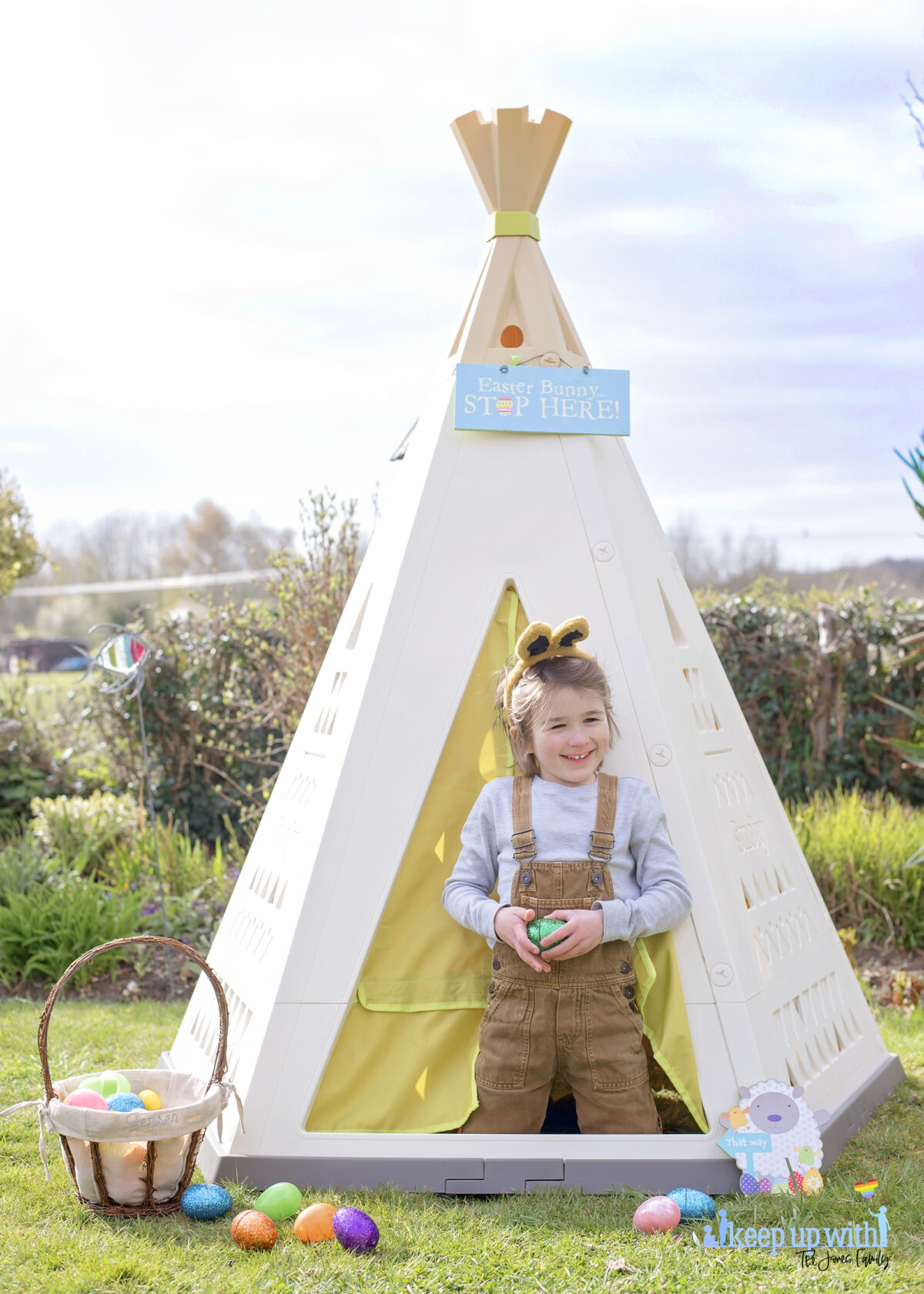 Image shows the new SmobyUK Teepee, available on Amazon, in the garden. The teepee is cream, white and green with a triangle pattern on the sides.  There is a fabric door which is lime green and a little boy aged 6 is stood in the doorway, dressed in light tan dungarees and a pale blue top, and wearing grey and pink bunny ears for easter.   He is laughing.  There is an easter baskets filled with coloured easter eggs which have spilled onto the floor.  The teepee is decorated with a sign which reads Easter Bunny Stop here!