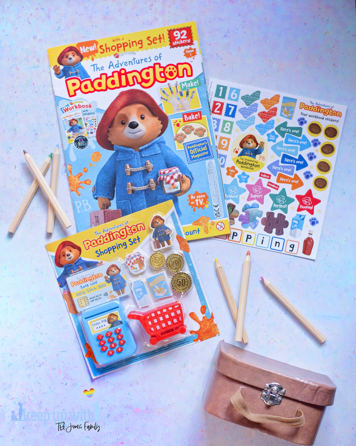 The Adventures of Paddington Bear Magazine EYFS. Picture shows issue one with free Paddington Shopping set laid out on blue background. Paddington's brown case is in the photograph.