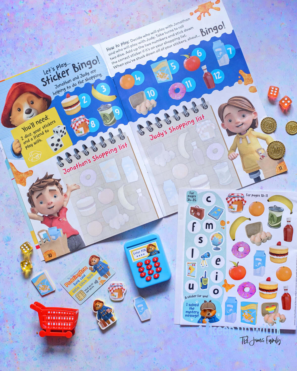 The Adventures of Paddington Bear Magazine EYFS. Photograph shows a spread of the magazine featuring a dice throwing game to calculate the cost of shopping for the under sixes.  There are coloured dice and stickers to help with the activity.