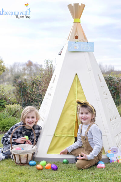 Smoby Teepee. Image shows Cream and White teepee with lime green fabric curtain. Two boys dressed for easter with bunny ears sit outside of it, with baskets filled with coloured easter eggs which have spilled on the the floor They are laughing in the garden.