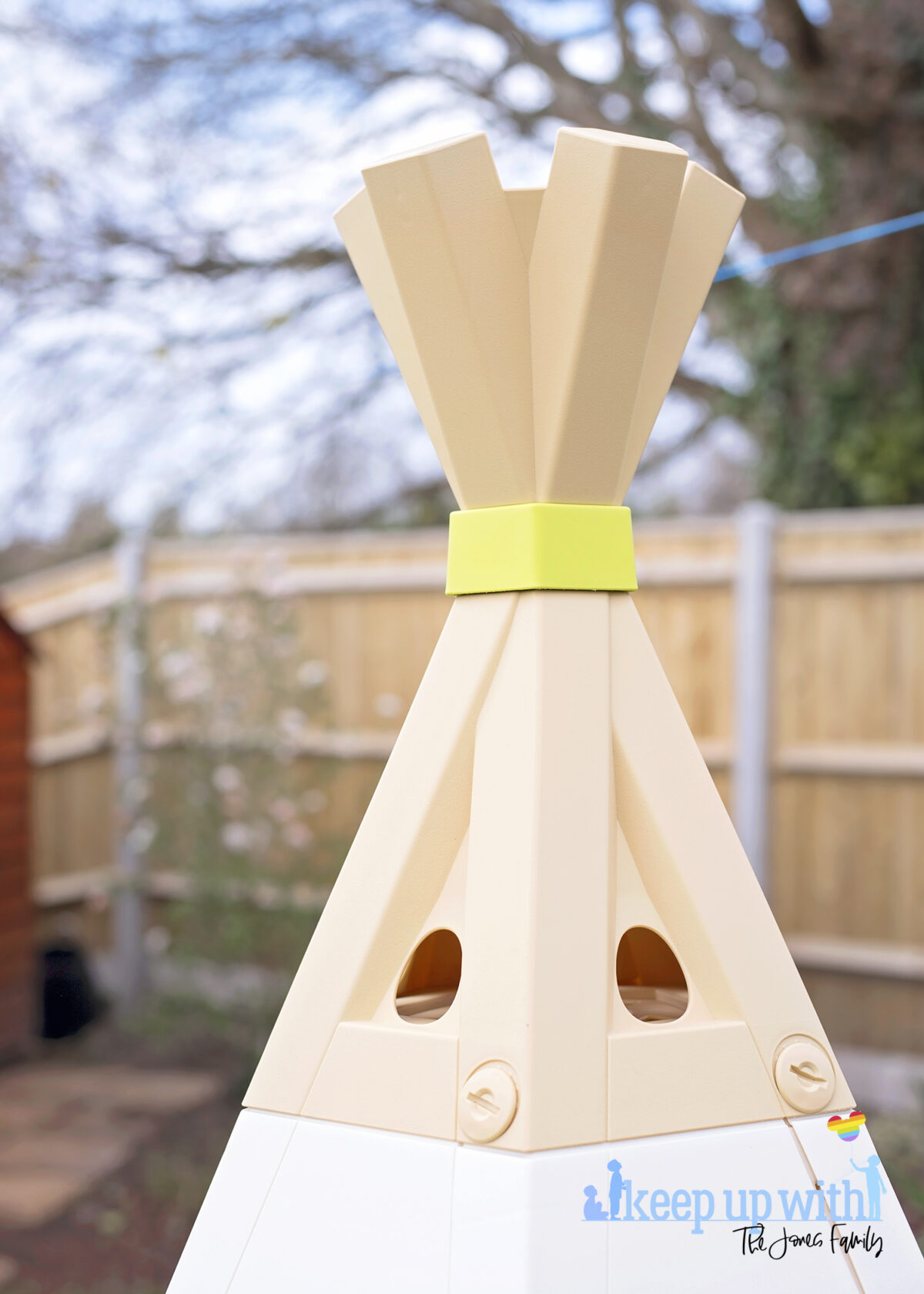 Image shows the new Smoby Teepee, available on Amazon, in the garden. The teepee is cream, white and green and the image shows the plastic teepee recreating the top part of a teepee where the wooden poles are crossed.