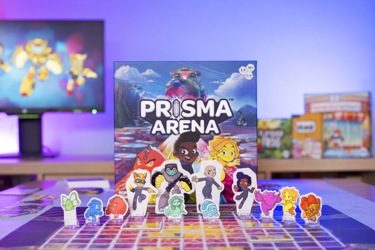 Prisma Arena Tabletop Game Box from Hub Games. Picture shows the box, board and all of the heroes and mo'kons on display.