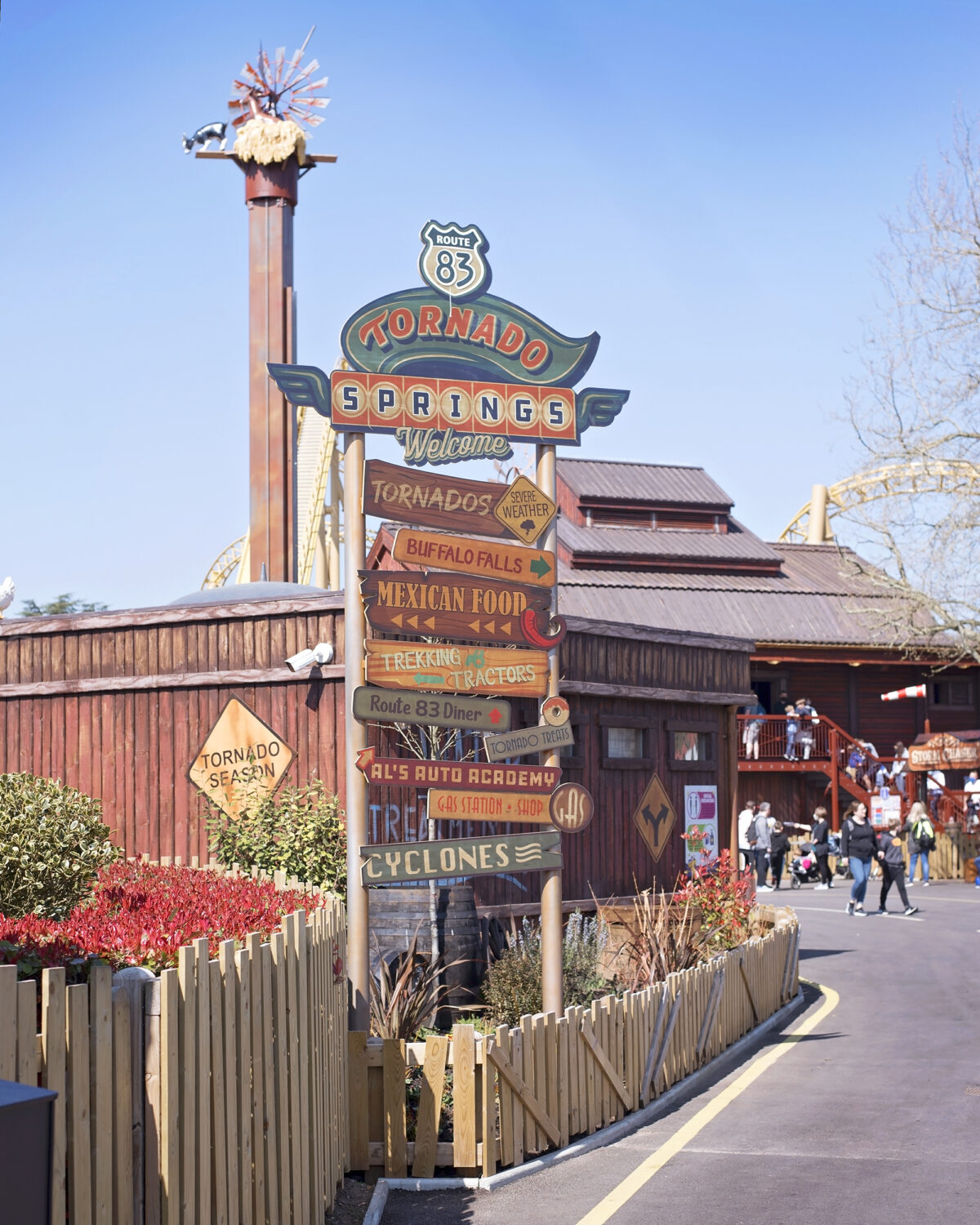 Image shows a directional signpost in Paultons Park Tornado Springs. Made of wood, the names of the rides in the theme park are listed on each arrow.