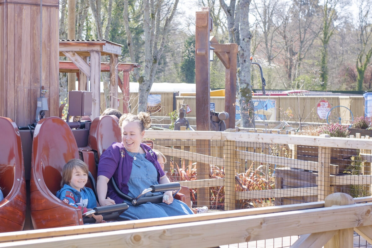 Image shows a mother and son seated on the Windmill Falls ride at Tornado Springs, Paultons Park, Hampshire.
