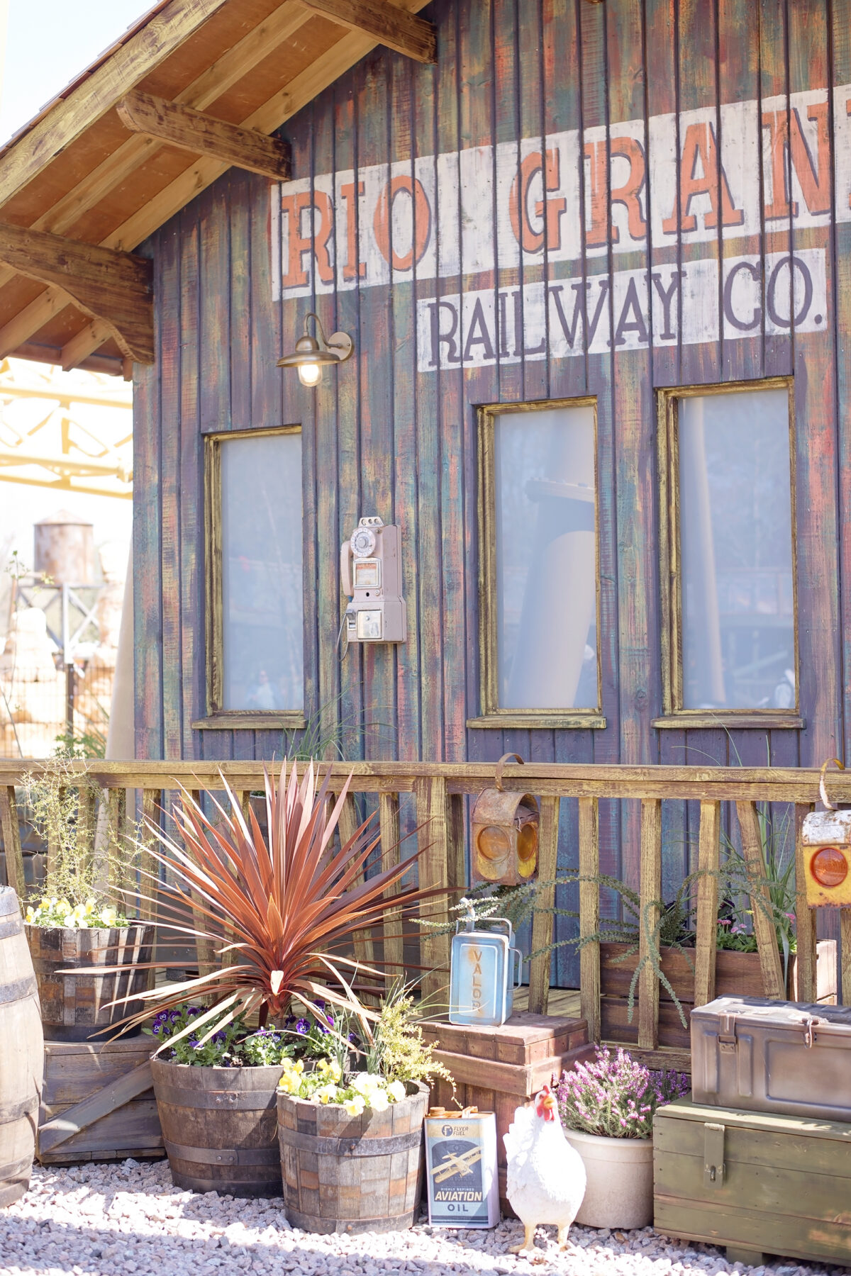Image shows theming at Paultons Park Tornado Springs area. An american wooden building belonging to the rio grande railway company. There is a white chicken walking on the porch, with flowers in barrels and cans of aviation oil littered next to ammunition cases.