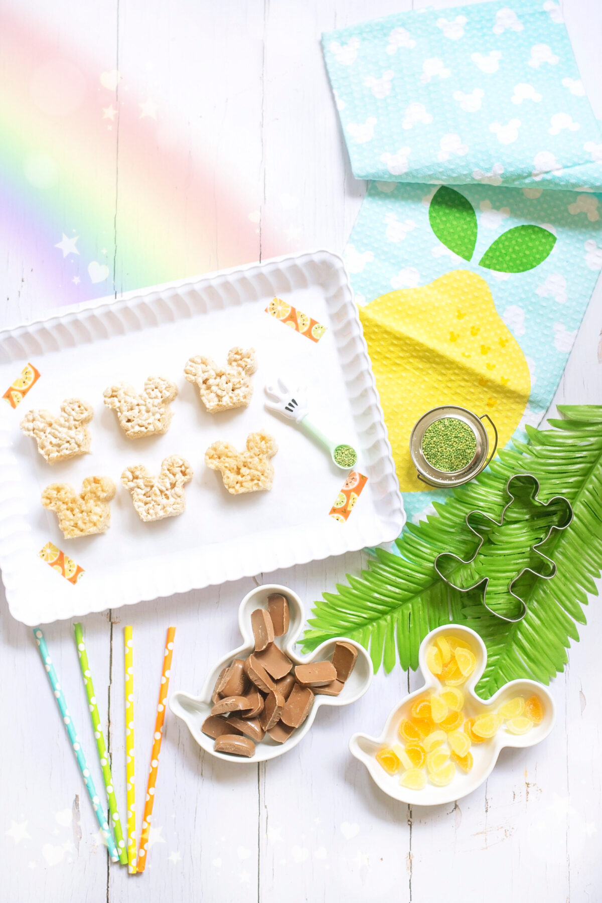 Image shows scalloped tray of summer themed Mickey Mouse Rice Krispie Treats surrounded by orange and lemon slices and tropical leaves, Disney tea towels and Minnie Mouse straws. All of the ingredients for the recipe are laid out on the tray including a DIsney's Mickey Mouse cookie cutter.