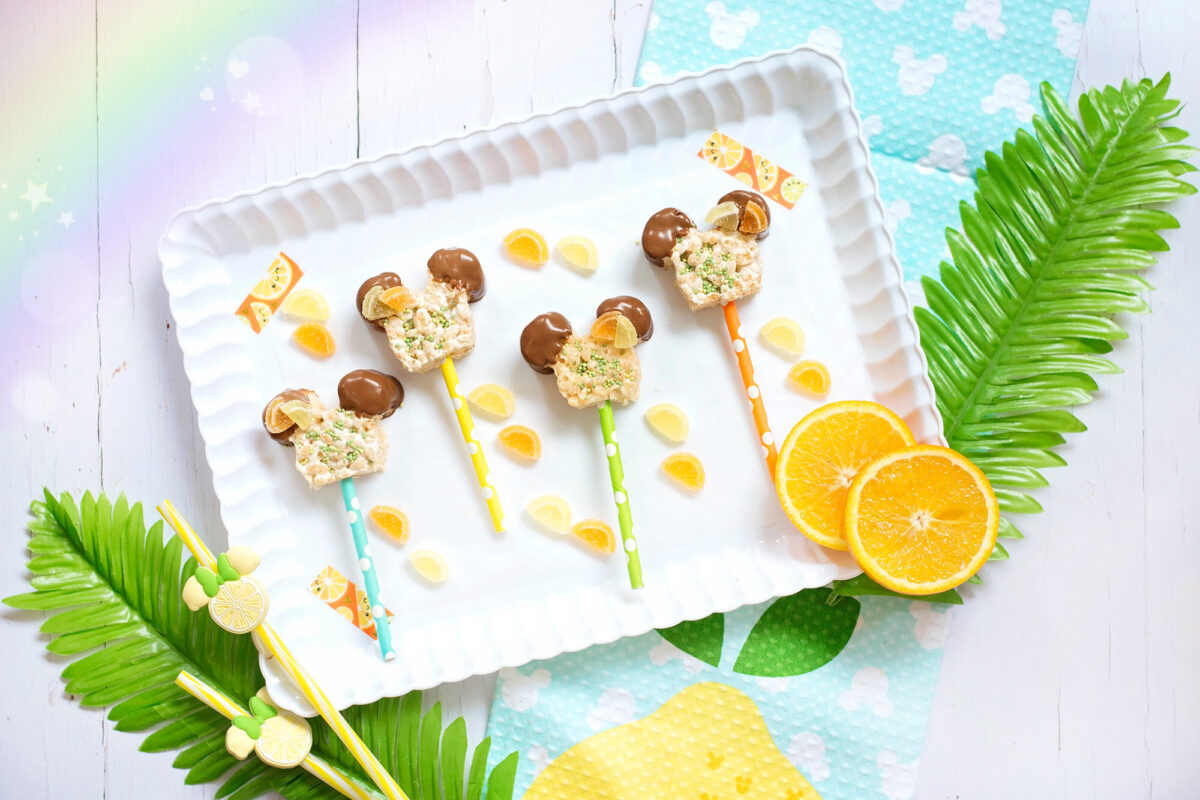 Image shows scalloped tray of summer themed Mickey Mouse Rice Krispie Treats surrounded by orange and lemon slices and tropical leaces, Disney tea towels and Minnie Mouse straws.