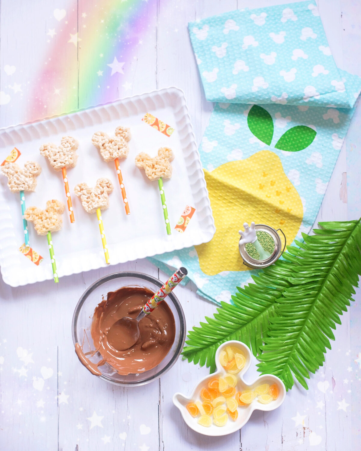 Image shows scalloped tray of summer themed Mickey Mouse Rice Krispie Treats surrounded by orange and lemon slices and tropical leaves, Disney tea towels and Minnie Mouse straws. There is a bowl of melted chocolate ready to dip the Mickey Mouse treats into.
