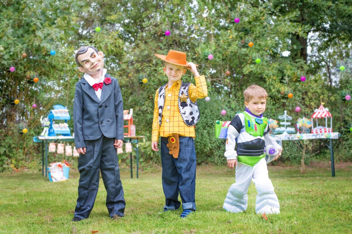 Image shows three of the Jones boys standing in their party dress up clothes ready for the Disney Toy Story Birthday party. One is Buzz Lightyear, one is Woody the Cowboy, and the third is dressed like the ventriloquist's dummy from Toy Story 4 who help Gabby.  They are outside in the garden and there are party tables behind them.