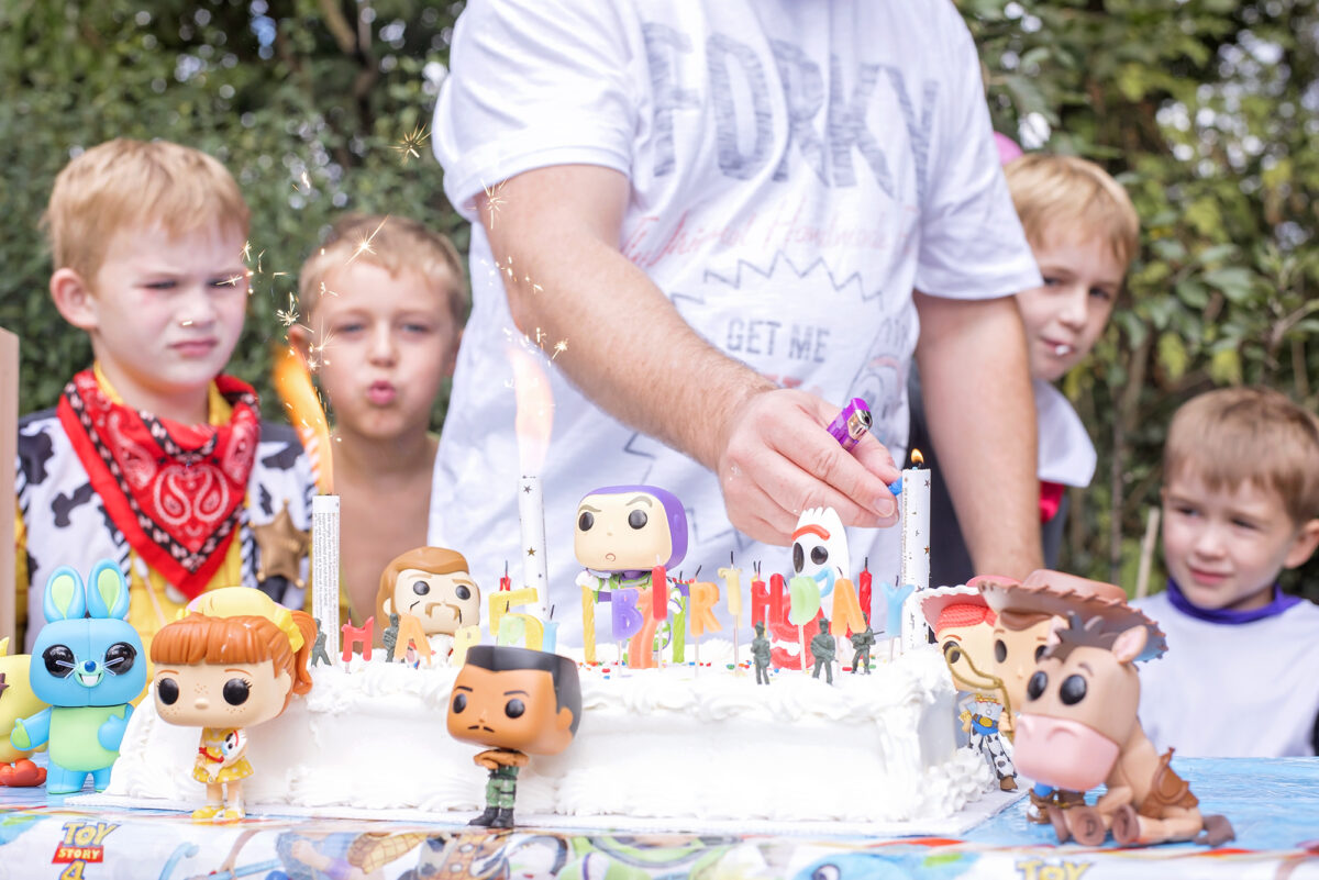 Image shows a large white Costco cake covered in Toy Story 4 Pop Funko toys.  Combat Carl, Woody, Bullseye, Gabby, Bunny and Ducky, Buzz, Jessie, Forky and Duke kaboom can be seen.  In the background there is an adult lighting the candles on the cake and the children of the jones family are watching.
