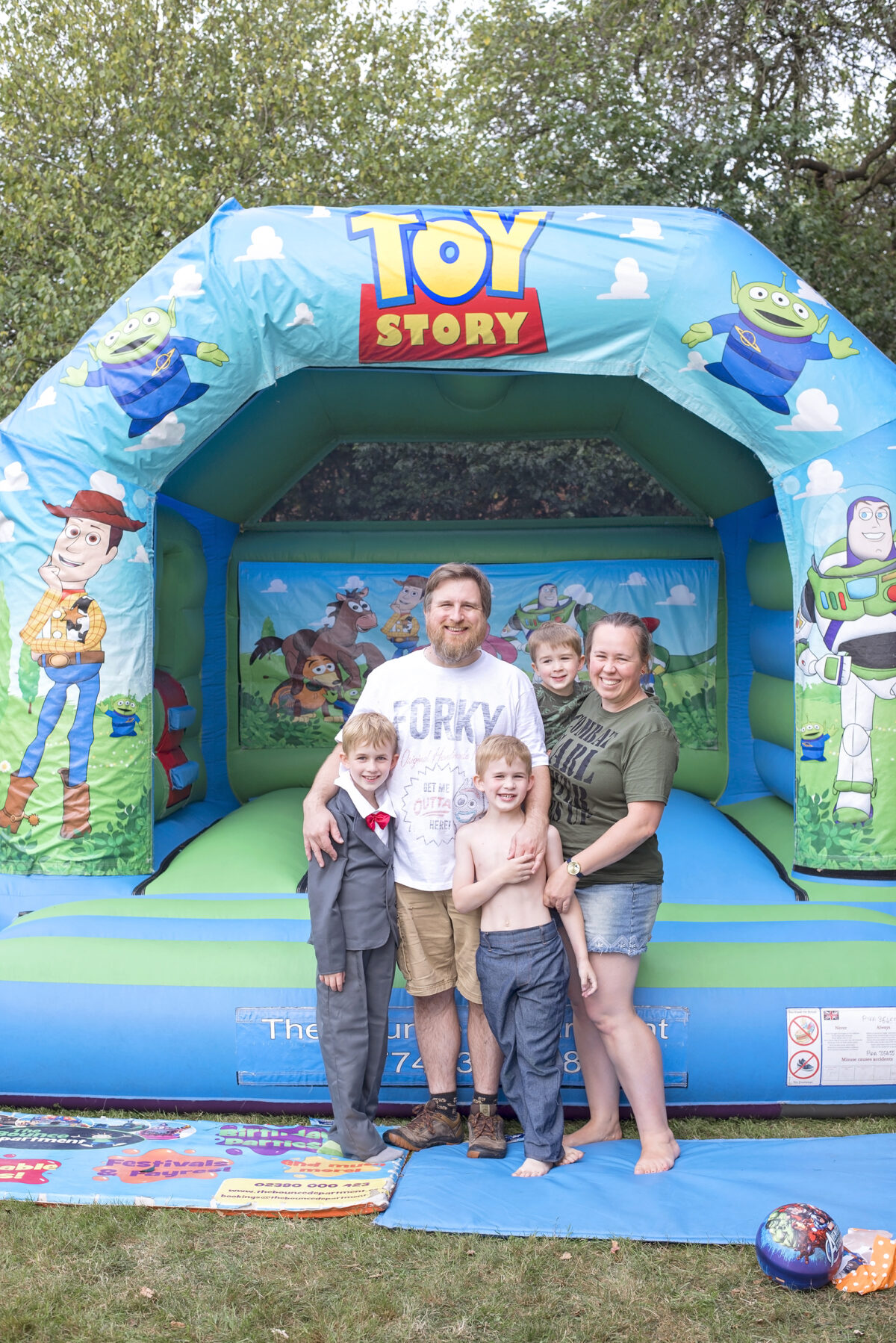 Image shows a toy story inflatable castle and a the Jones family stood next to it.