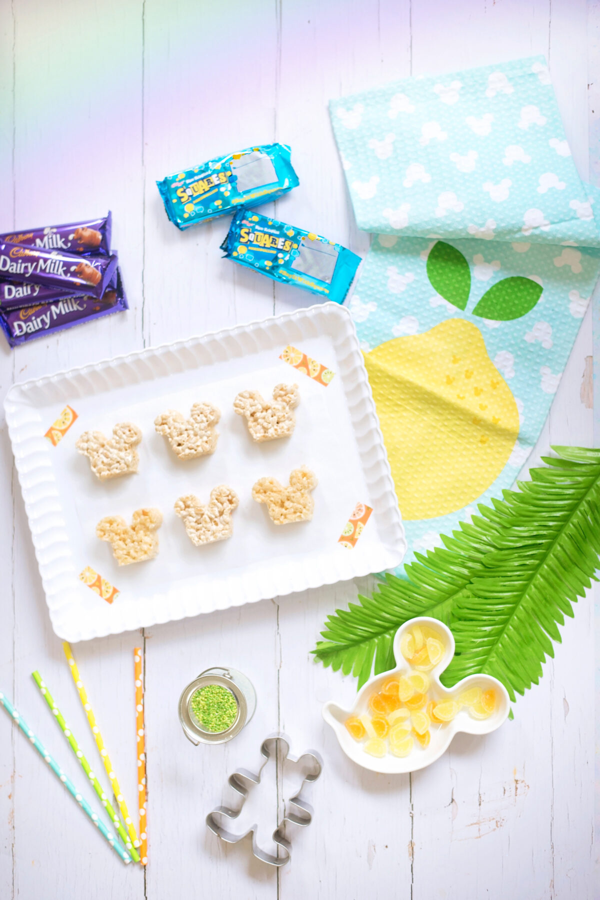 Image shows all of the ingredients needed to make the summer themed Disney's Mickey Mouse Rice Krispie Treats. Dairy Milk chocolate bars, rice krispie squares, green sprinkles, orange and lemon slices.  They are laid ona white wooden backdrop with a Mickey Mouse lemon tea towel and a white scalloped tray, with a Mickey Mouse cookie cutter and coloured spotted paper straws.