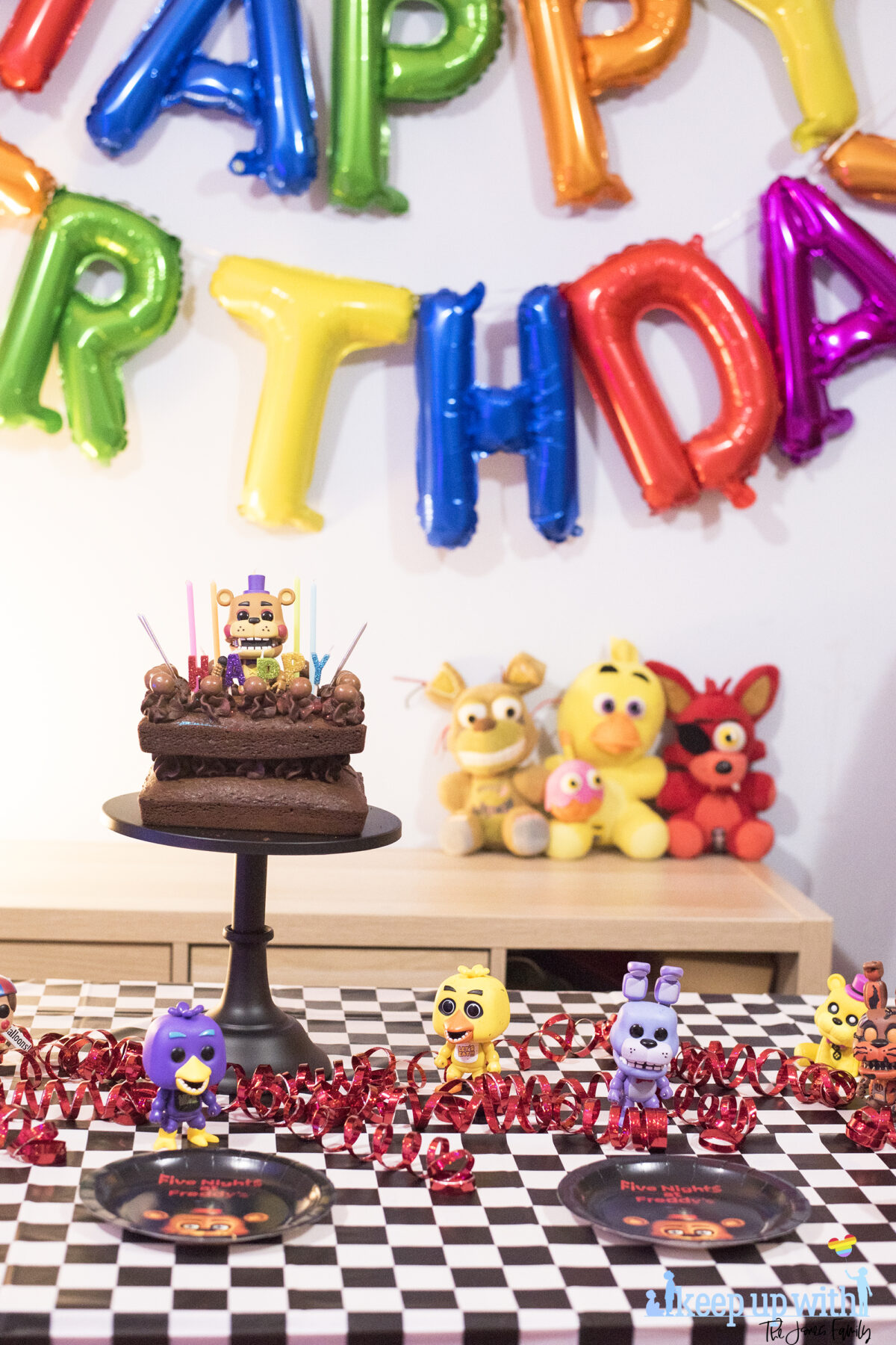 How to throw a Five Nights at Freddy's Party. Image shows a party table covered in a black checkered tablecloth, happy birthday spelled out in rainbow coloured balloons as a garland across the wall, three FNAF plushies; Foxy, Chica and Plushtrap sat on the sideboard and a chocolate cake on a black cake pedestal with a Funko Pop Viny; Rockstar Freddy on top of it. Image by Keep Up With The Jones Family